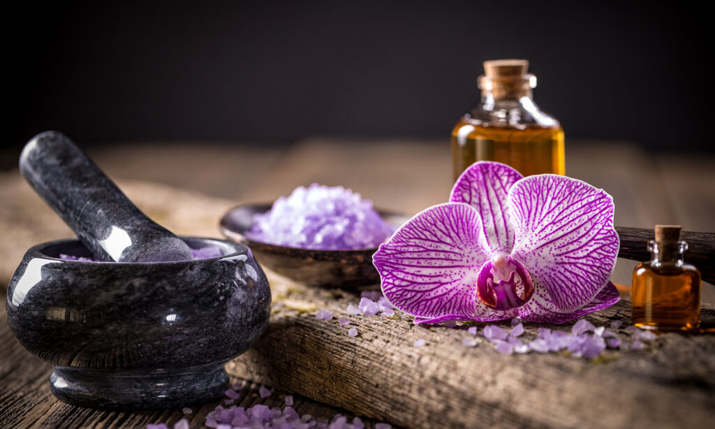 violet flower next to essential oil bottle